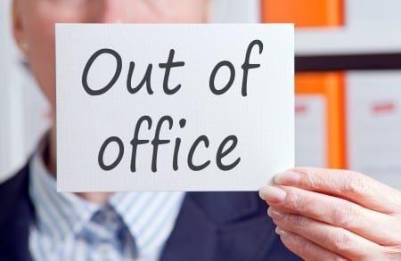 Business man holding up a notice saying out of office