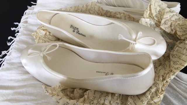 White wedding shoes with the words Pure and Precious written on the inside