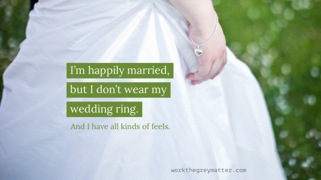 Picture of a bride's right hand against the skirt of her white wedding dress, wearing a silver bracelet with a heart locket attached. Over the picture are the words: I'm happily married, but I don't wear my wedding ring. And I have all kinds of feels. workthegreymatter.com