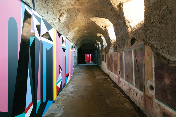 Modern art installation opposite Roman wall paintings in corridor in Pompeii