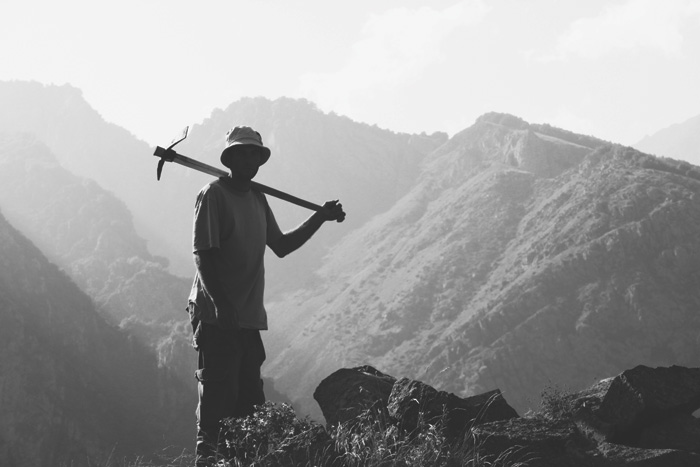 Archaeologist with mattock in Caucasus Mountains