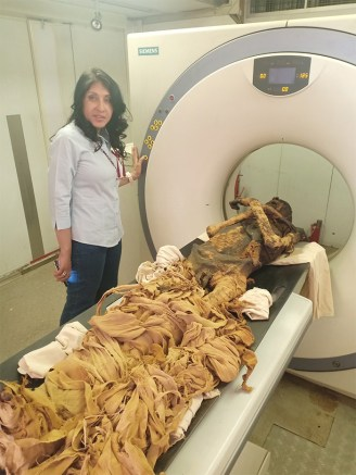 The mummy lying on the CT scanner with a researcher standing next to it