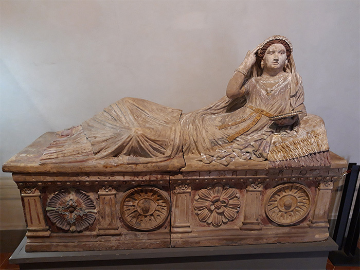 A terracotta painted sarcophagus depicting a woman reclining on top, wearing an ornate dress and veil, and holding a mirror.