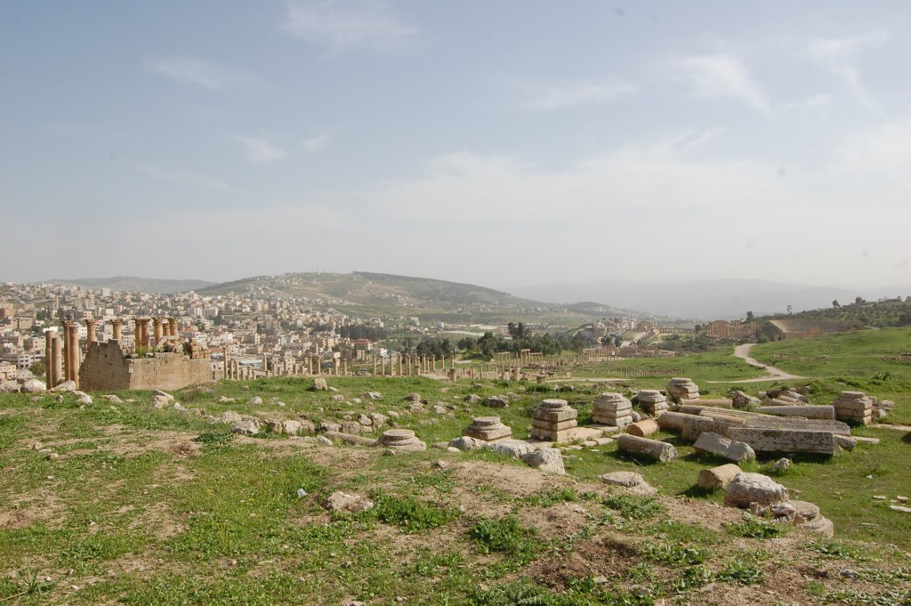The ruins of Jerash, with the remains of columns in the centre and taller columns still standing to the left, with the city and hills in the distance.