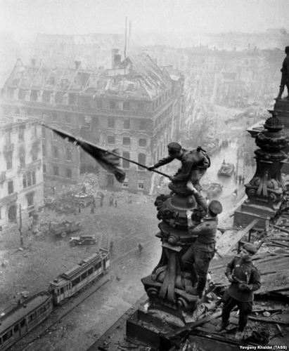 Berlin. Germany. Soldiers hanging soviet flag in the honour of victory on the Reichstag building. (Photo ITAR-TASS/ Yevgeny Khaldei) Германия. 2 мая 1945 г. Бойцы 8-й гвардейской армии: Алексей Ковалёв (со знаменем), Абдулхаким Исмаилов и Леонид Горычев водружают Знамя Победы над Рейхстагом. Халдей Евгений/Фотохроника ТАСС