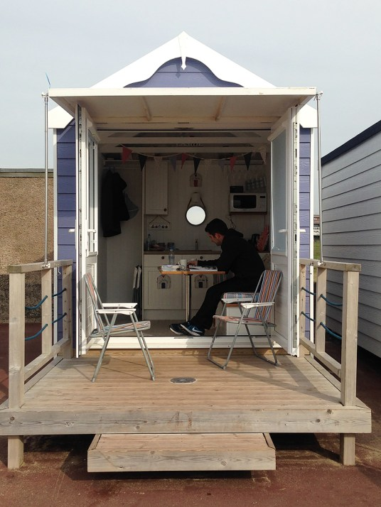 View of the beach hut from outside with man reading inside