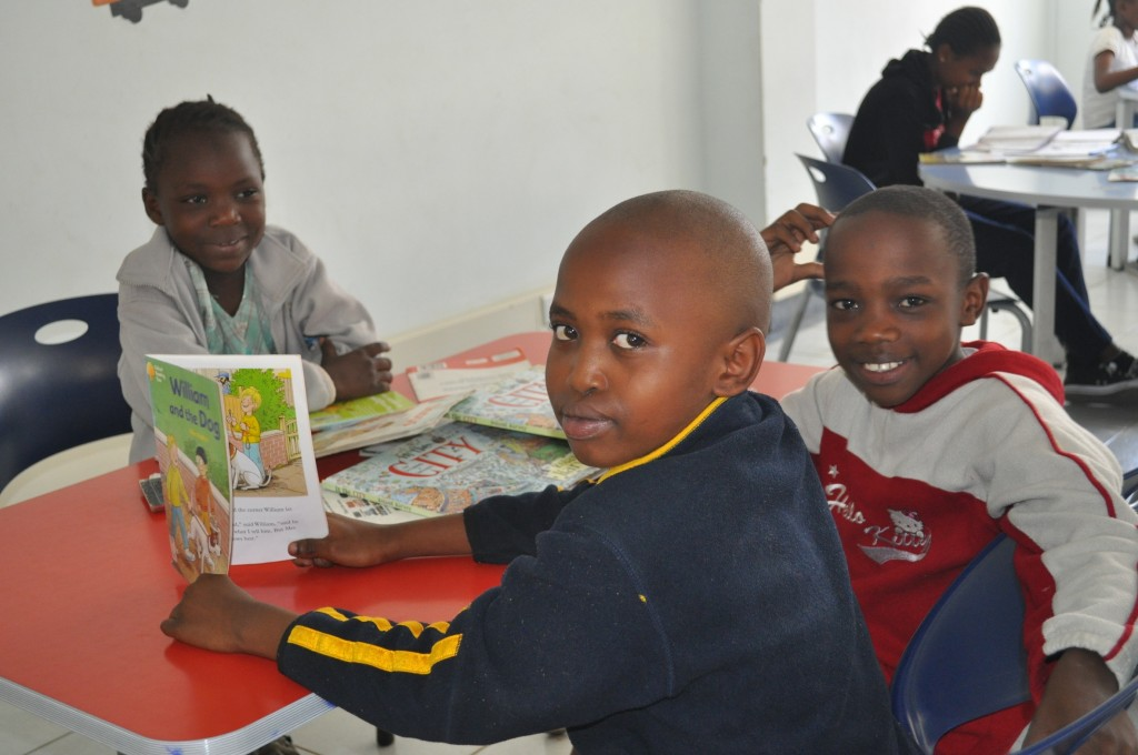 A young boy enjoys his new book in Buru Buru library, Kenya
