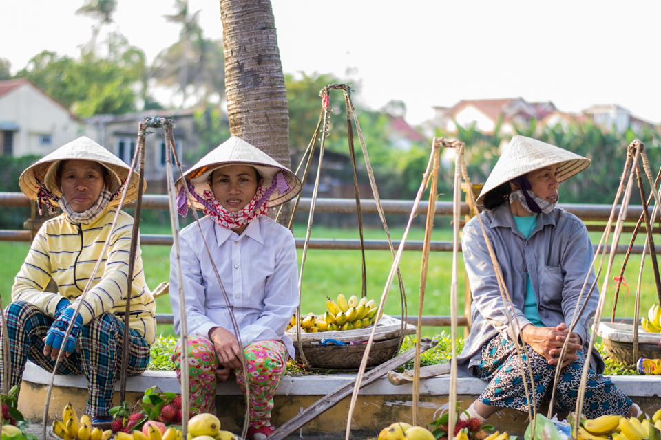 3 Vietnamese women in traditional cone hats selling fruit