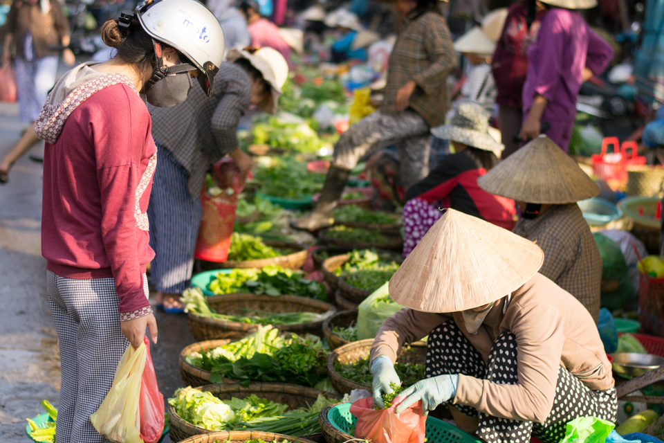 Woman buying fresh vegetables from Hoi An Central market