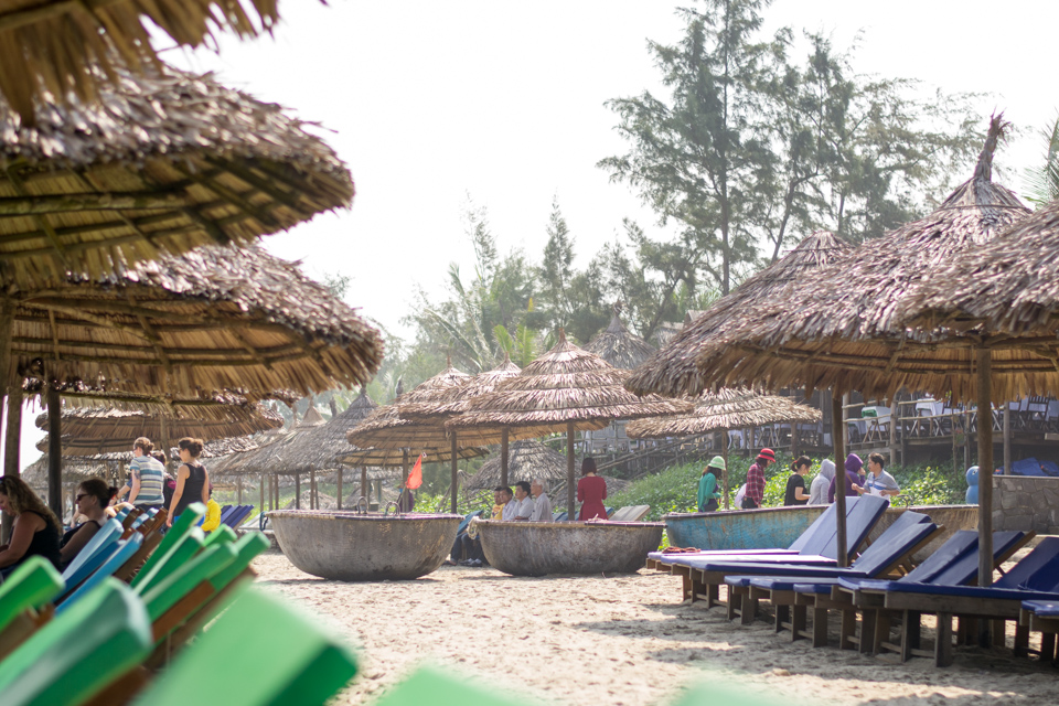 Bamboo basket boats and lounge chairs under thatched umbrellas