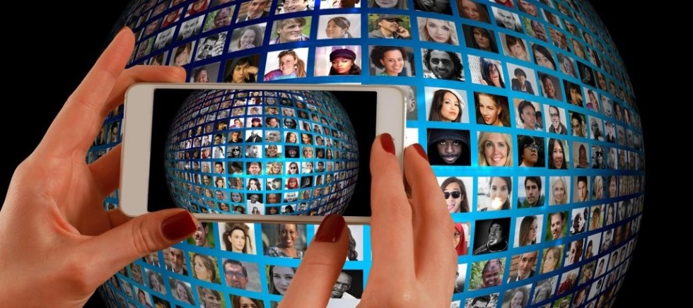 Hands holding phone taking photo of globe filled with people to learn how to find clients as a freelancer