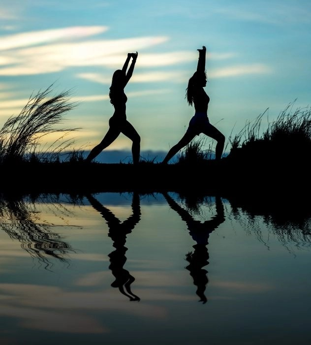 Two women in yoga poses by a body of water at night, a good way to exercise when you're self employed working online