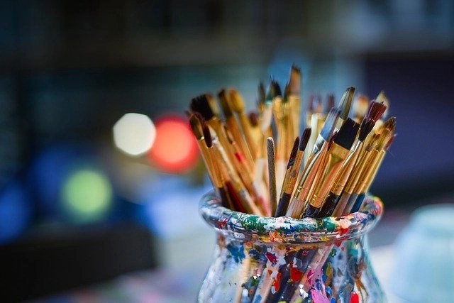 Dozens of small paintbrushes in paint-dabbled glass jar used by a freelance artist