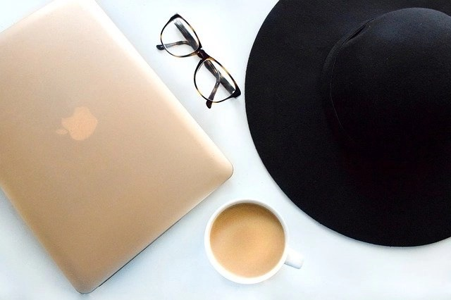 Learn how to become a blogger and make money blogging with a gold MacBook, cup of coffee, pair of glasses and a hat