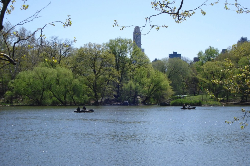 Water with two canoes floating in Central Park in April 2010 with trees and buildings in the background