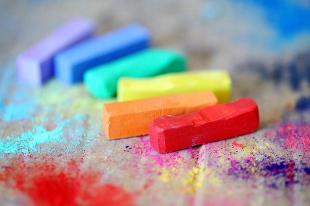 6 colorful pieces of chalk on a table representing 6 creative work-at-home jobs