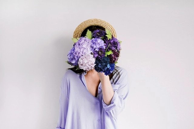 Female Freelancer Thinking About Etsy Products, In Purple Blouse With Straw Hat Hiding Her Face With A Bouquet Of Purple Flowers