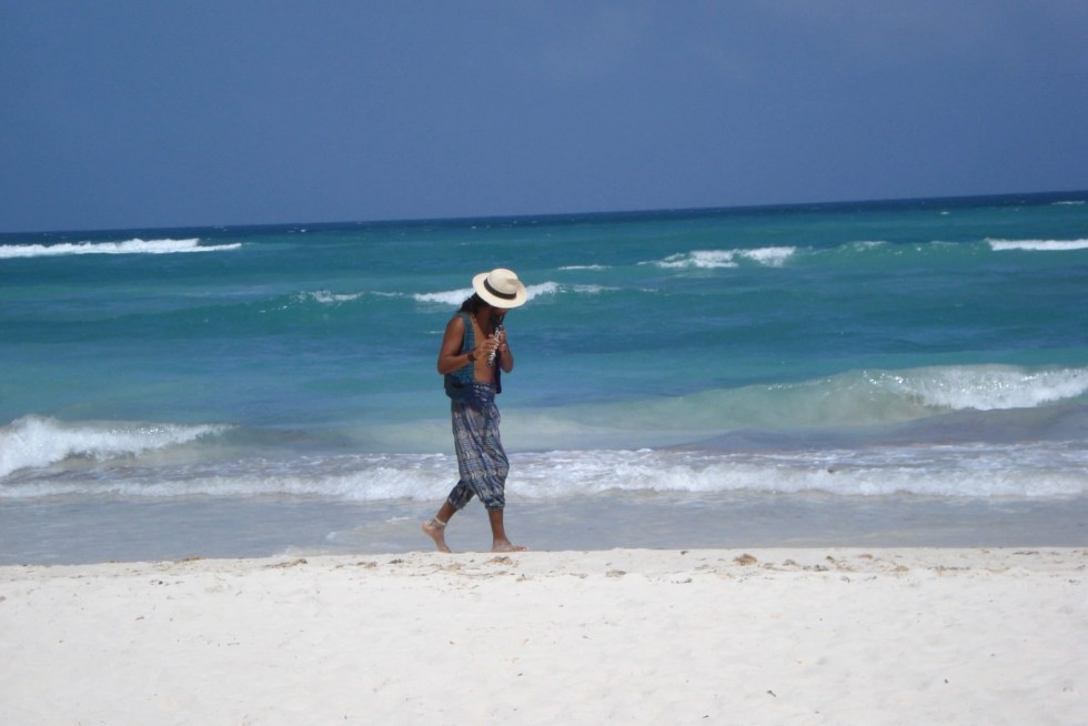 Guy walking along Mexico beach playing a flute