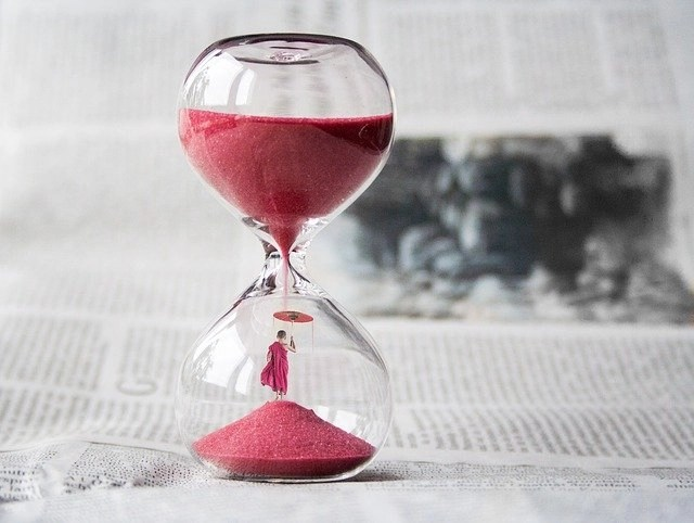 Red sand in hourglass signifying saving time in this TextExpander review