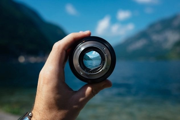 Hand holding camera lens seeing how to succeed at freelancing