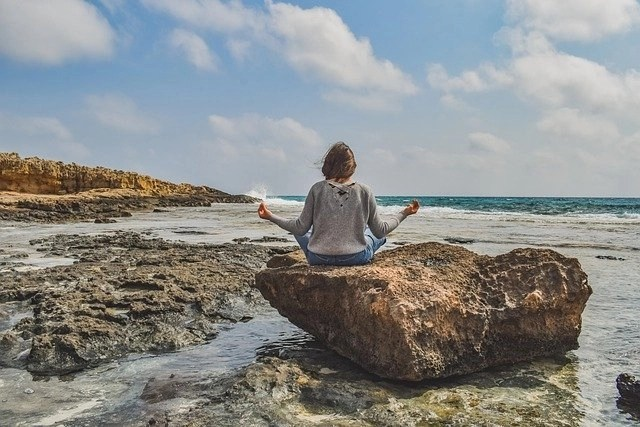 Female freelance writer with writer's block meditating on a rock on the edge of an ocean