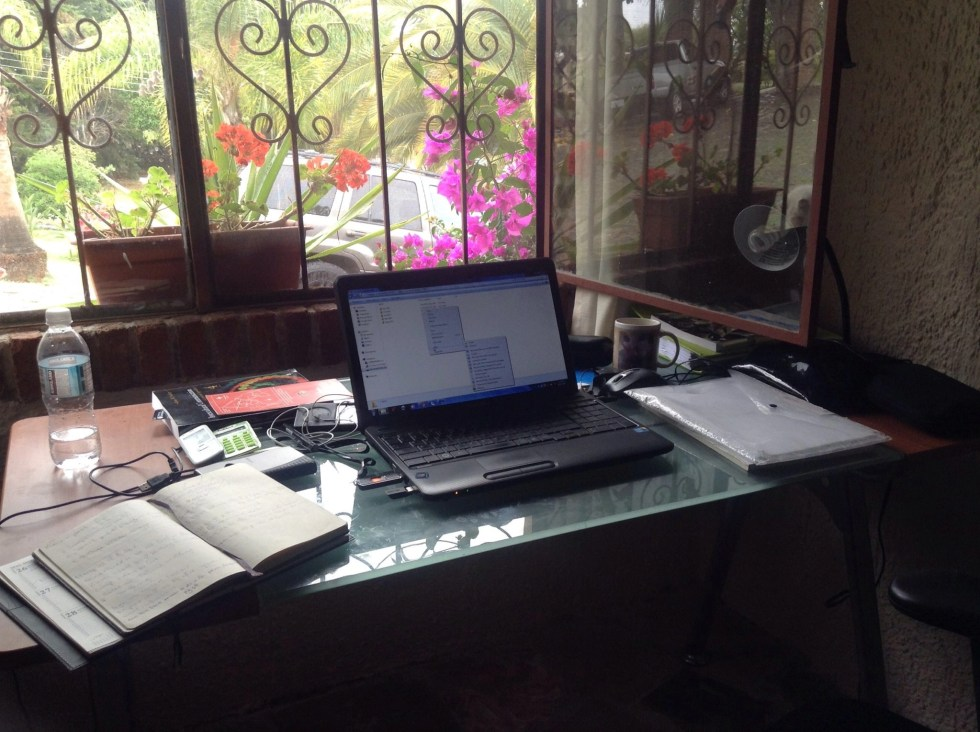 Open laptop, book, bottle of water and other items on a desk in front of a window in Mexico