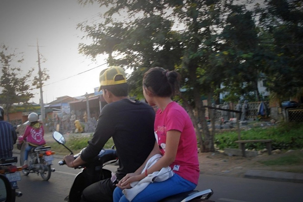 Man on motorbike with woman behind him riding sidesaddle on the road to Kampot, Cambodia