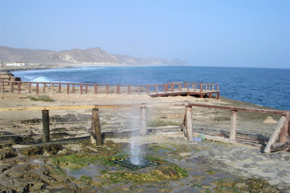 Water shooting up a few feet out of a metal grate in an area fenced off by a low-slung wooden fence, with mountains and the Arabian Sea in the background