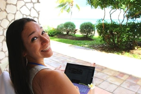 Vicky Sosa with her iPhad, smiling in front of a beautiful garden and sea, the ideal digital nomad lifestyle