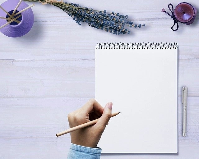 Woman's left hand holding pencil, about to write in steno notebook with pen on the right side atop a purplish table with purple decorations.