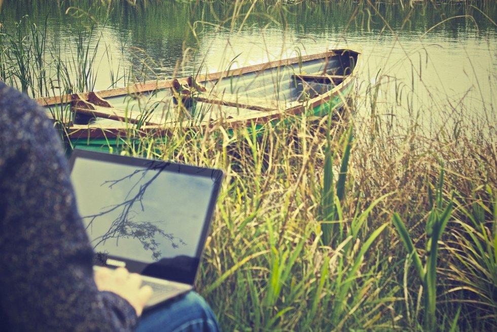 Man working remotely on a laptop alongside a canoe in a lake