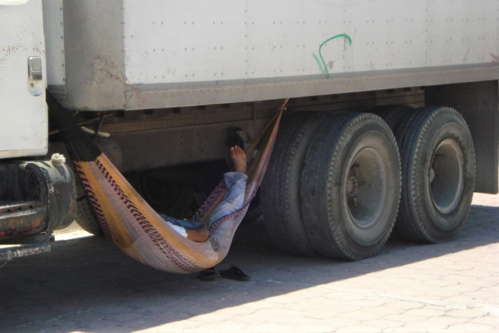 Man sleeping in a hammock under a truck on Isla Mujeres, Mexico, not far from the famous Chichen Itza ruins