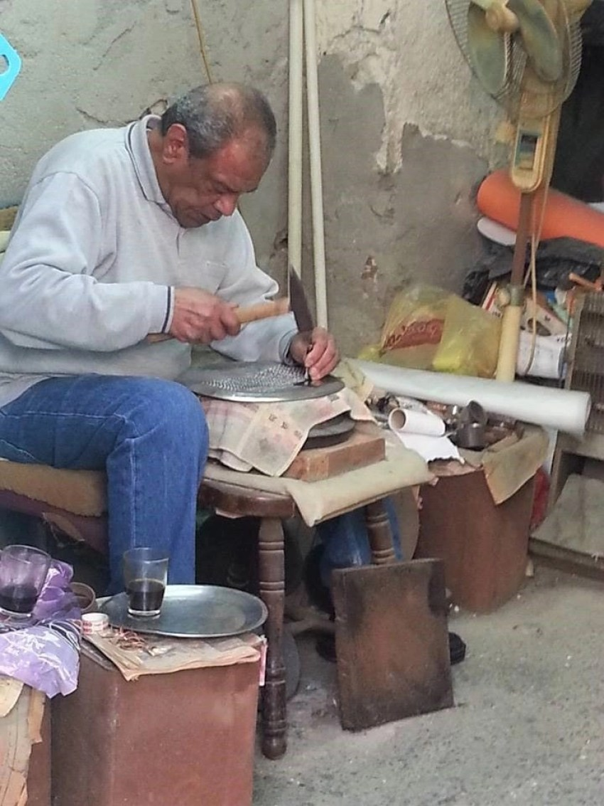 Man using a hammer to engrave metal in the Middle East marketplace Souq Al Abiad in Akko, Israel