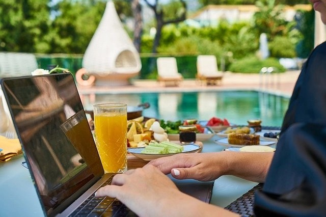 Woman studying how to become a scopist poolside with delicious food while traveling