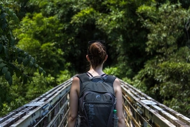 Woman who enjoys working and traveling, walking across a bridge with her backpack
