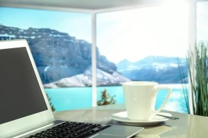Laptop and white coffee cup on table surrounded by glass windows overlooking rocky mountain and blue water is something you can experience when you travel and work