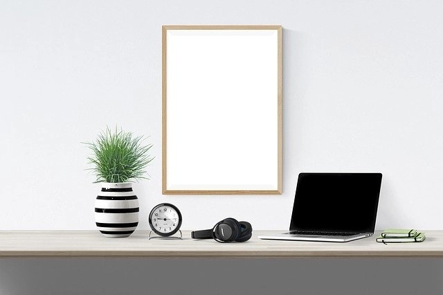 Simple, Clean Work Station To Do Transcription Jobs- Desk With Laptop, Headphones, Clock, Small Plant And White Board On The Wall