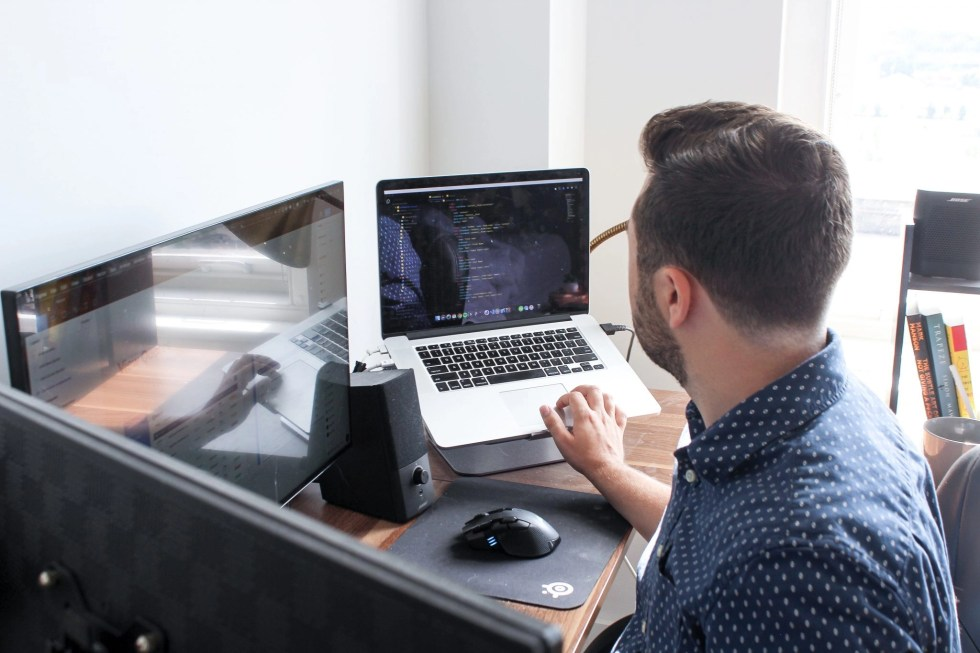 Man facing away from camera working on his side hustle on a laptop mounted on stand at a desk