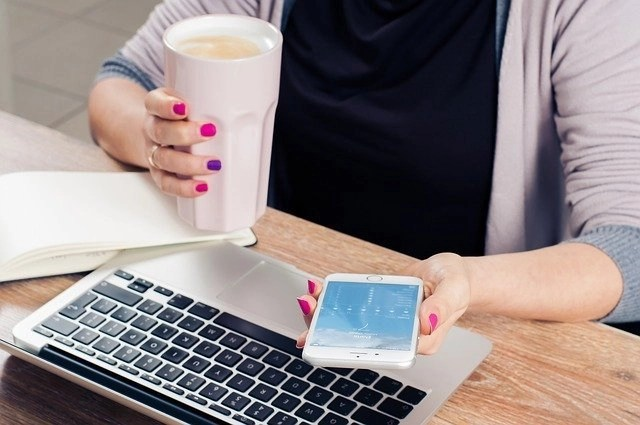 Female Pinterest virtual assistant with purple and pink nail polish at laptop, holding iPhone and a tall white cup