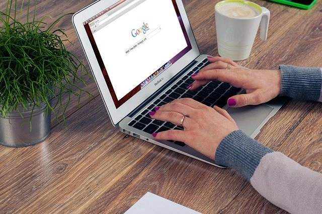 Woman's hands on laptop researching multiple income streams with Google search page pulled up