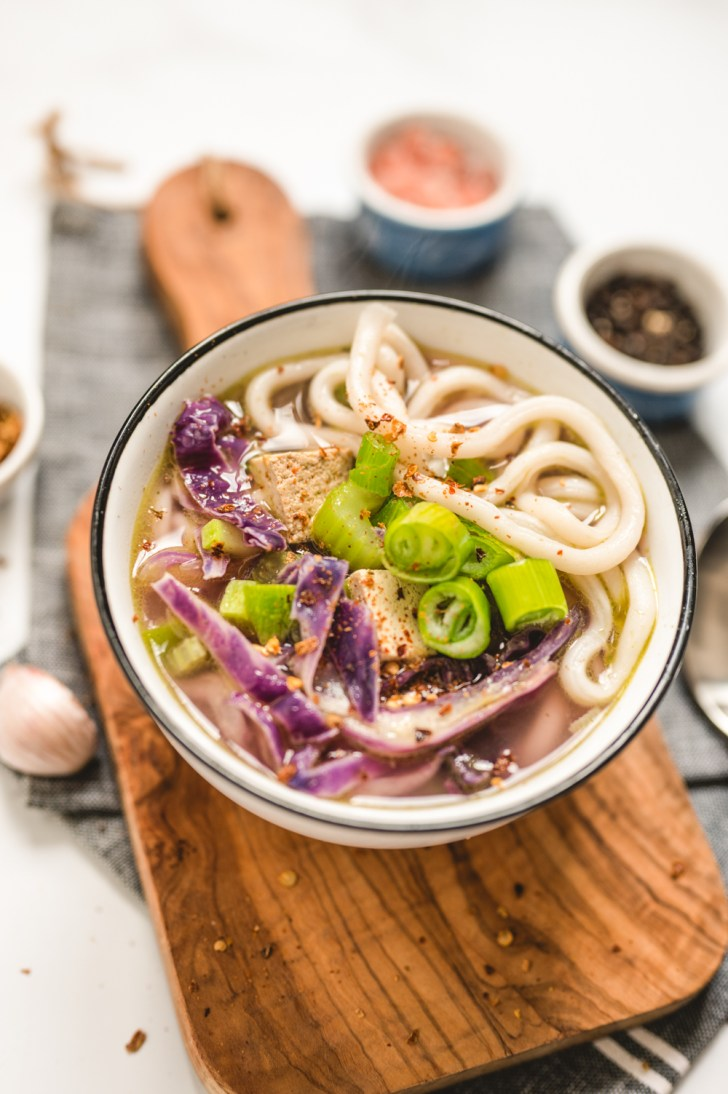 Bowl of Purple Udon Noodle Soup Served over a Wooden Board Close Up