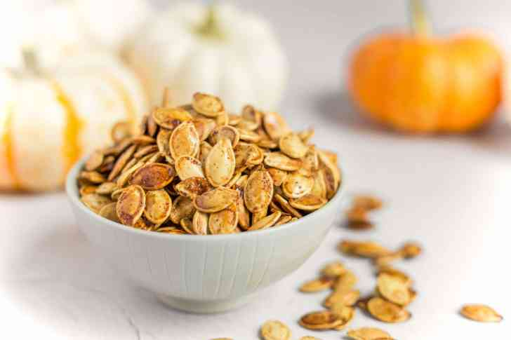 Best Roasted Pumpkin Seeds Recipe Served in a Bowl Surrounded by Pumpkins