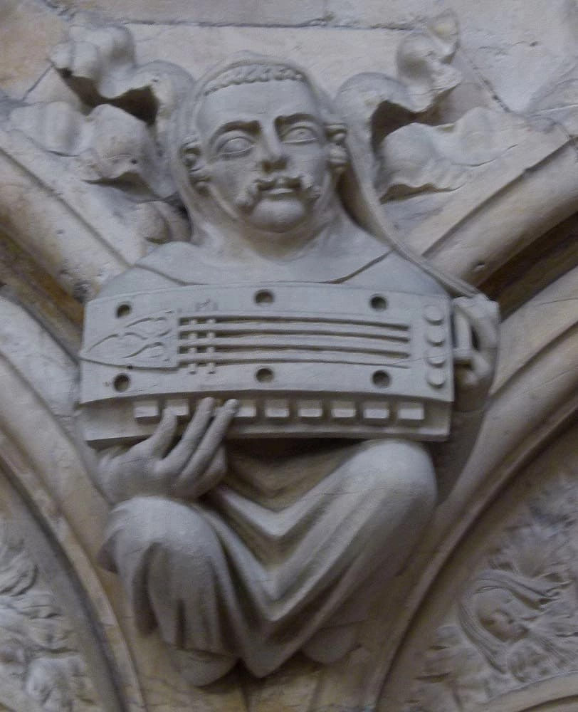 Stone minstrel with hurdy-gurdy