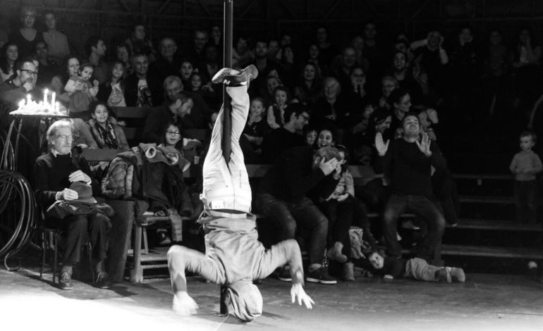 Devant la surprise du public, un des jeunes de la troupe se laisse tomber du haut du mat, seulement accroché avec ses pieds ©Malika Barbot/Worldzine