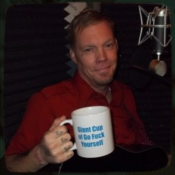 "Jeff Done, Reno musician and singer, holding Rev. Rory's coffee mug that reads ""Giant Cup of Go Fuck Yourself"""