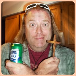 Bill Ware holding a small wooden cross and a can of beer.