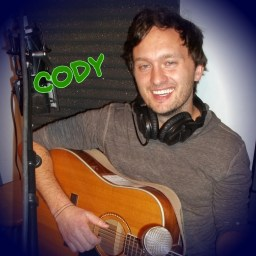 Cody Thomas of Low La La, a unique Reno NV duo, holding a guitar and smiling