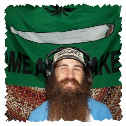 "John Underwood, Smiling through a very large beard and wearing a ball cap that says ""Shootdang"" and sitting in front of a green banner with a lit joint that reads ""Come and take"""