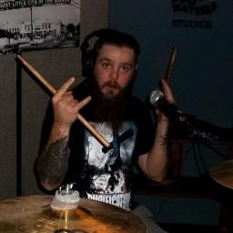 Scott Tobin at his drumkit, flashing rock hands