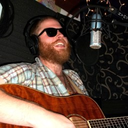 Lex White laughing over his guitar with a full red beard